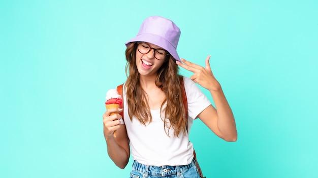Jonge mooie vrouw die er ongelukkig en gestrest uitziet, zelfmoordgebaar maakt een pistoolteken met een ijsje. zomer concept