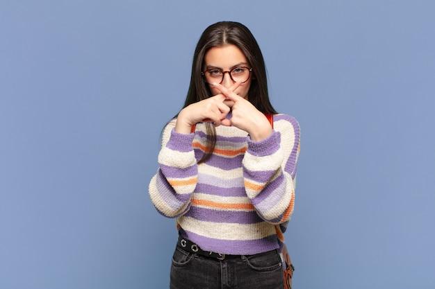 Jonge mooie vrouw die er serieus en ontevreden uitziet met beide vingers vooraan gekruist in afwijzing