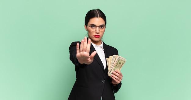 Jonge mooie vrouw die er serieus, streng, ontevreden en boos uitziet met een open palm die een stopgebaar maakt. bedrijfs- en bankbiljettenconcept
