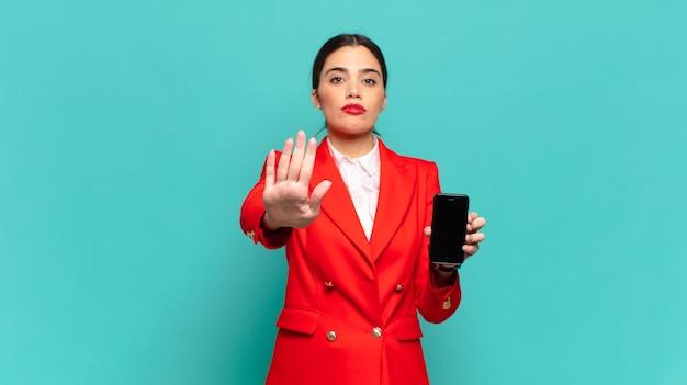 Jonge mooie vrouw die er serieus, streng, ontevreden en boos uitziet met een open palm die een stopgebaar maakt. slimme telefoon concept