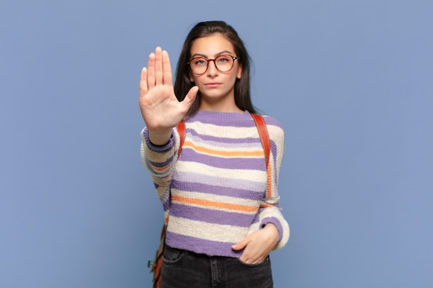 Jonge mooie vrouw die er serieus, streng, ontevreden en boos uitziet met een open palm die een stopgebaar maakt. studentenconcept