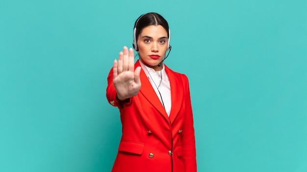 Jonge mooie vrouw die er serieus, streng, ontevreden en boos uitziet met een open palm die een stopgebaar maakt. telemarketeer concept