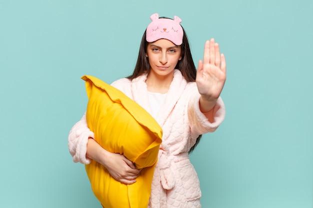 Jonge mooie vrouw die er serieus, streng, ontevreden en boos uitziet met een open palm die een stopgebaar maakt. wakker worden met pyjama's concept