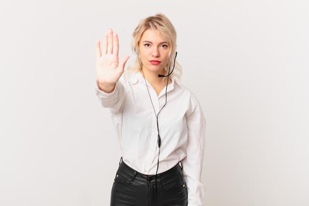 Jonge mooie vrouw die er serieus uitziet en open palm toont die een stopgebaar maakt. telemarketing concept