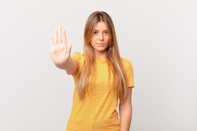Jonge mooie vrouw die er serieus uitziet en open palm toont die een stopgebaar maakt