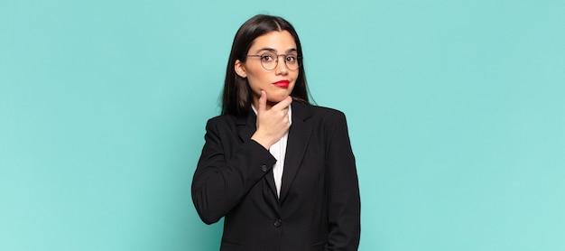 Jonge mooie vrouw die er serieus, verward, onzeker en attent uitziet, twijfelend tussen opties of keuzes. bedrijfsconcept