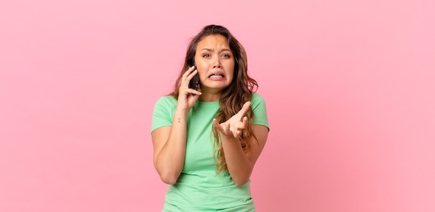 Jonge mooie vrouw die er wanhopig, gefrustreerd en gestrest uitziet en een smartphone vasthoudt
