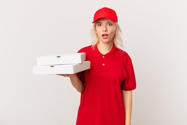 Jonge mooie vrouw die erg geschokt of verrast kijkt. pizza bezorgconcept