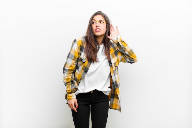Jonge mooie vrouw die ernstig en nieuwsgierig kijkt, luistert, probeert een geheim gesprek of roddel te horen, afluisteren geïsoleerd tegen witte muur