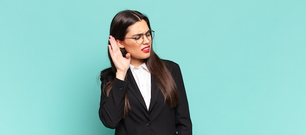 Jonge mooie vrouw die ernstig en nieuwsgierig kijkt, luistert, probeert een geheim gesprek of roddel te horen, afluistert