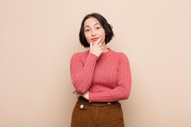 Jonge mooie vrouw die ernstig, nadenkend en wantrouwend kijkt, met één arm gekruist en hand op kin, wegingsopties over beige muur