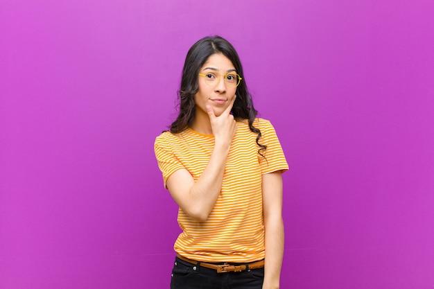 Jonge mooie vrouw die ernstig, nadenkend en wantrouwend kijkt, met één arm gekruist en hand op kin, wegingsopties over paarse muur