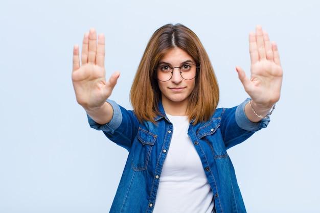 Jonge mooie vrouw die ernstig, ongelukkig, boos en niet bevallen toegang verbiedt of einde met beide open palmen zegt