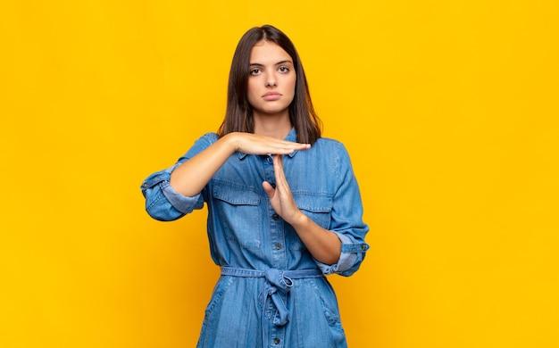 Jonge mooie vrouw die ernstig, streng, boos en ontevreden kijkt en time-outteken maakt