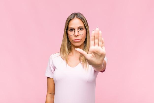 Jonge mooie vrouw die ernstig, streng, ontevreden en boos kijkt die open palm toont die stopgebaar maakt