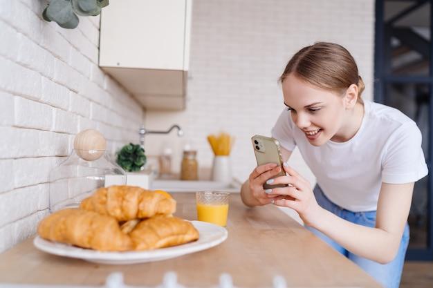 Jonge mooie vrouw die foto op mobiele telefoon van croissants neemt