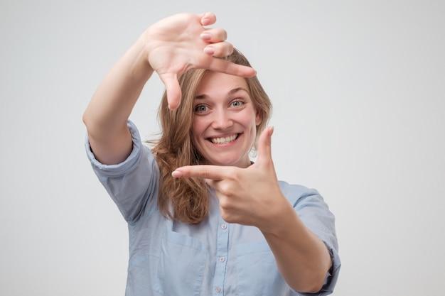 Jonge mooie vrouw die frame met haar handen het glimlachen maakt