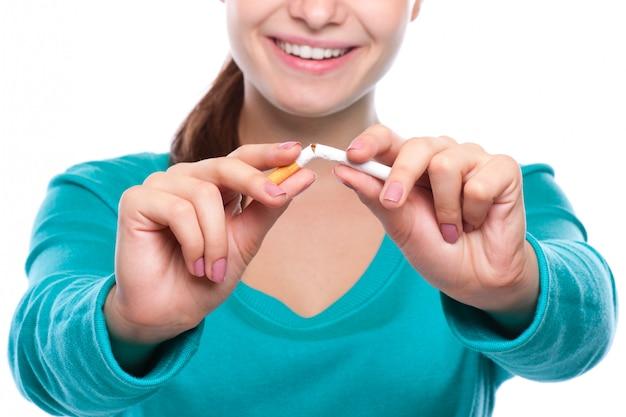 Jonge mooie vrouw die gebroken sigaret vooraan houdt.