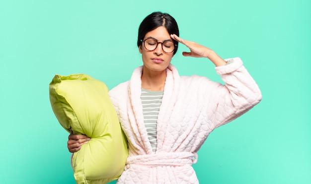 Jonge mooie vrouw die geconcentreerd, attent en geïnspireerd kijkt, brainstormend en verbeeldend met de handen op het voorhoofd. pyjama's concept