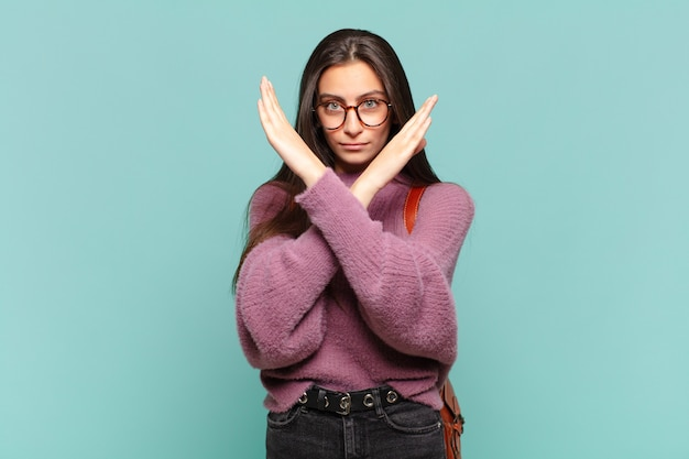 Jonge mooie vrouw die geïrriteerd en ziek van je houding kijkt, zegt genoeg! handen gekruist vooraan om te zeggen dat je moet stoppen. studentenconcept
