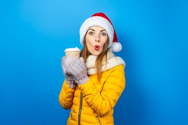 Jonge mooie vrouw die geïsoleerde hoed van de kerstman draagt