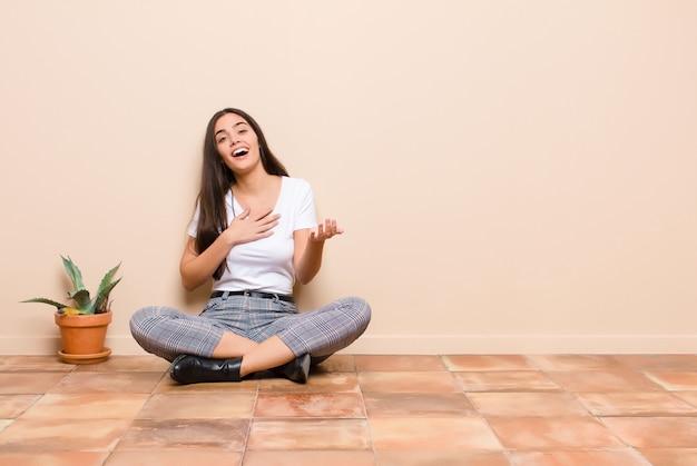 Jonge mooie vrouw die gelukkig en verliefd voelt, glimlachend met de ene hand naast het hart en de andere uitgerekt vooraan zittend op een vloer