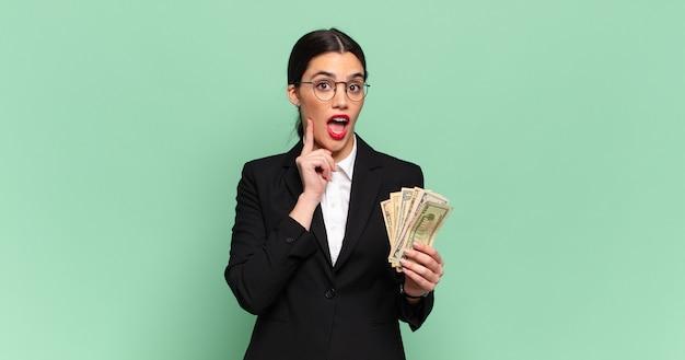 Jonge mooie vrouw die gelukkig glimlacht en dagdroomt of twijfelt, kijkend naar de kant. zaken en bankbiljetten concept
