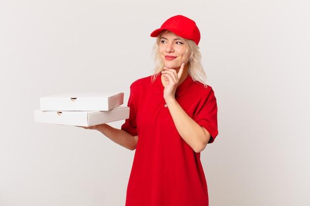 Jonge mooie vrouw die gelukkig glimlacht en dagdroomt of twijfelt. pizza bezorgconcept