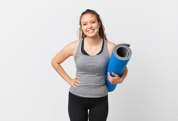 Jonge mooie vrouw die gelukkig glimlacht met een hand op de heup en zelfverzekerd en een yogamat vasthoudt