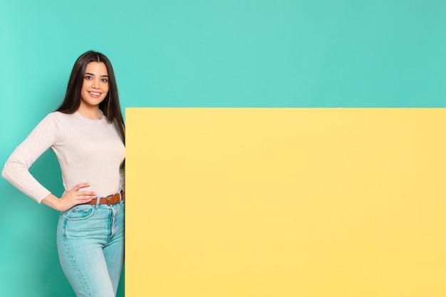 Jonge mooie vrouw die gelukkig glimlacht met een hand op heup en zelfverzekerde, positieve, trotse en vriendelijke houding. kopieer ruimte om uw concept te plaatsen