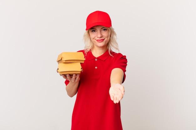 Jonge mooie vrouw die gelukkig glimlacht met vriendelijk en een concept aanbiedt en toont. hamburger bezorgconcept