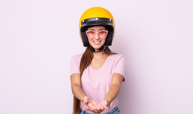 Jonge mooie vrouw die gelukkig glimlacht met vriendelijk en een concept aanbiedt en toont. motorrijder en helm