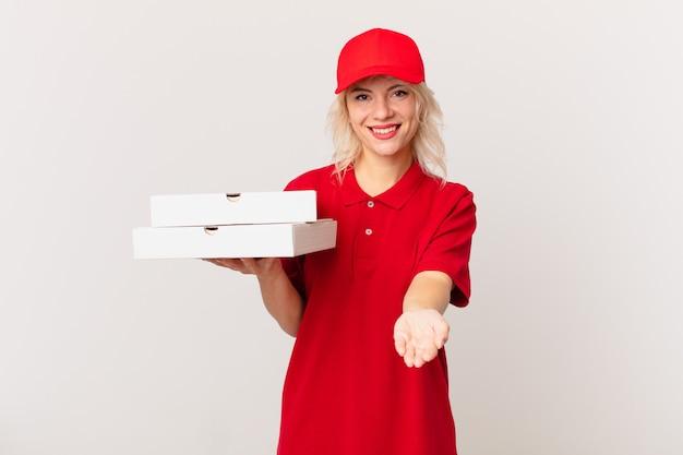 Jonge mooie vrouw die gelukkig glimlacht met vriendelijk en een concept aanbiedt en toont. pizza bezorgconcept