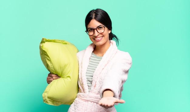 Jonge mooie vrouw die gelukkig glimlacht met vriendelijke, zelfverzekerde, positieve blik, die een voorwerp of concept aanbiedt en toont. pyjama's concept
