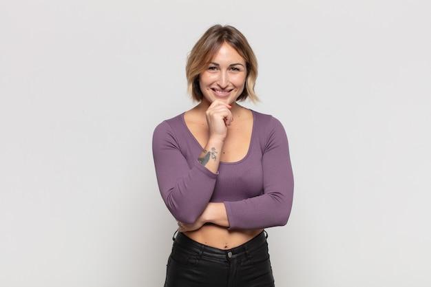 Jonge mooie vrouw die gelukkig kijkt en met hand op kin glimlacht, zich afvraagt of een vraag stelt, opties vergelijkt