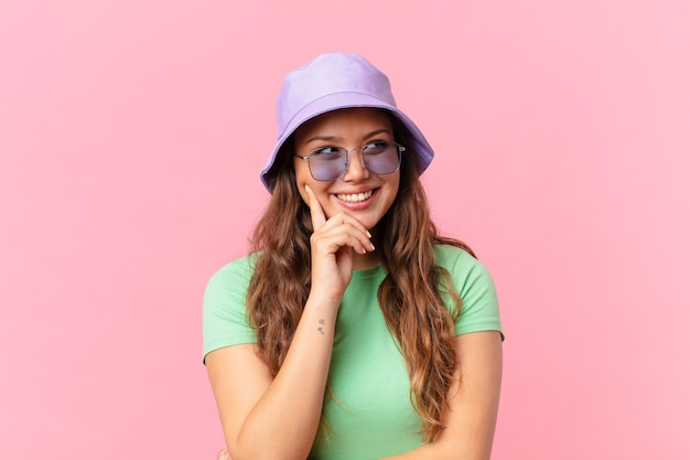 Jonge mooie vrouw die gelukkig lacht en dagdroomt of twijfelt. zomer concept