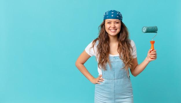 Jonge mooie vrouw die gelukkig lacht met een hand op de heup en zelfverzekerd en een muur schildert