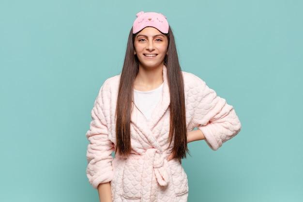 Jonge mooie vrouw die gelukkig lacht met een hand op de heup en zelfverzekerde, positieve, trotse en vriendelijke houding. wakker worden met pyjama's concept