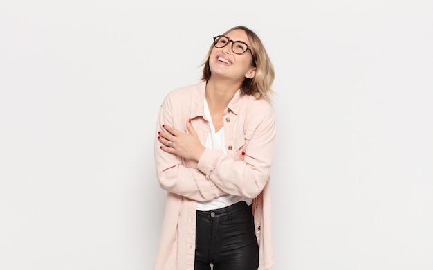 Jonge mooie vrouw die gelukkig lacht met gekruiste armen