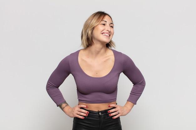 Jonge mooie vrouw die gelukkig, opgewekt en zelfverzekerd kijkt, trots glimlacht en met beide handen op de heupen naar kant kijkt