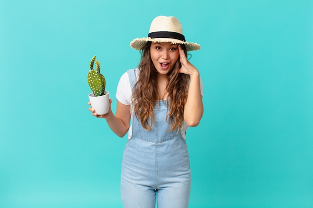 Jonge mooie vrouw die gelukkig, verbaasd en verrast kijkt en een cactus vasthoudt