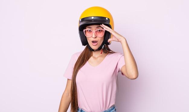 Jonge mooie vrouw die gelukkig, verbaasd en verrast kijkt. motorrijder en helm