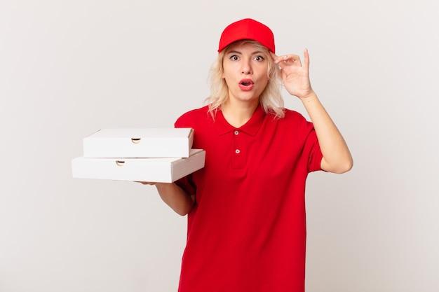 Jonge mooie vrouw die gelukkig, verbaasd en verrast kijkt. pizza bezorgconcept