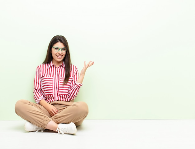 Jonge mooie vrouw die gelukkig, verrast en vrolijk voelt, glimlachend met positieve houding, die een oplossing of een ideezitting op de vloer realiseert