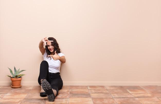 Jonge mooie vrouw die gelukkig, vriendelijk en positief voelt, glimlachend en een portret of fotokader met handen maakt die een terrasvloer zitten