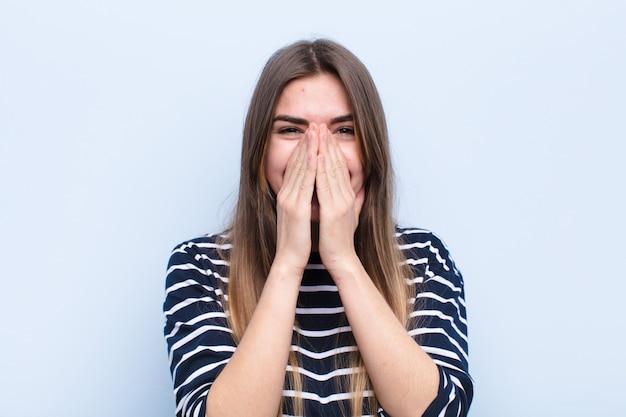 Jonge mooie vrouw die gelukkig, vrolijk, gelukkig en verrast bedekkend mond met beide handen tegen zachte blauwe muur kijkt