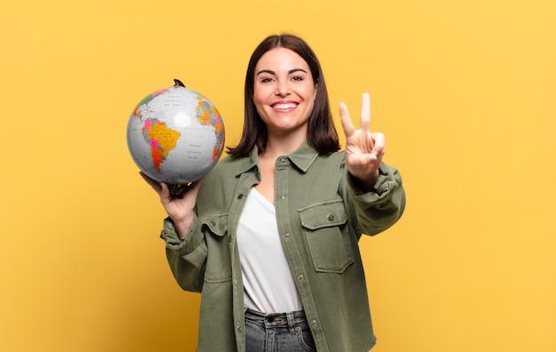 Jonge mooie vrouw die gelukkig, zorgeloos en positief glimlacht en kijkt, overwinning of vrede met één hand gebaart