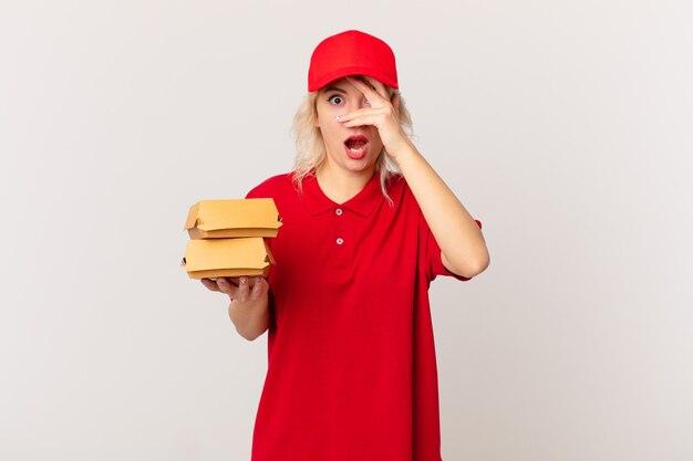 Jonge mooie vrouw die geschokt, bang of doodsbang kijkt en haar gezicht bedekt met de hand. hamburger bezorgconcept