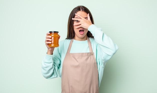 Jonge mooie vrouw die geschokt, bang of doodsbang kijkt en haar gezicht bedekt met de hand. perzik gelei concept