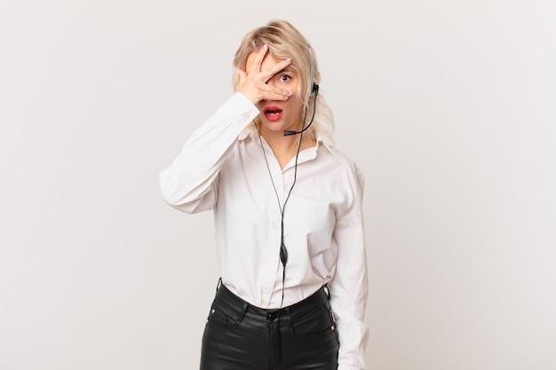 Jonge mooie vrouw die geschokt, bang of doodsbang kijkt en haar gezicht bedekt met de hand. telemarketing concept